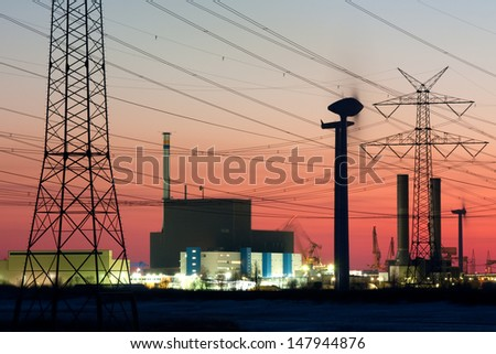 Nuclear power plant in Brunsbuettel, Germany, with Electric power pylons  and wind turbines at sunset - stock photo