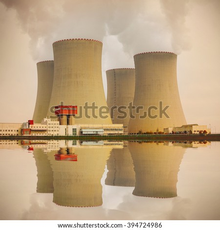 Nuclear power plant on the coast. Industrial and ecology disaster concept. Warm filtered picture. - stock photo