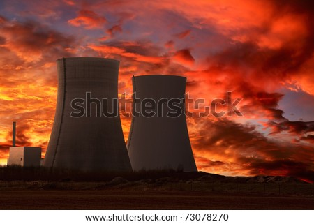 Nuclear power plant with an intense red and cloudy evening sky - stock photo
