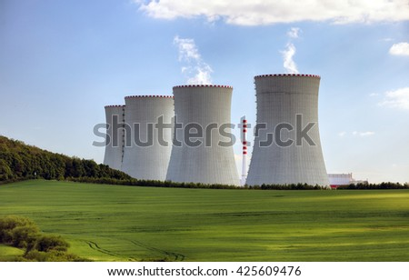 Nuclear power plant with green field. - stock photo