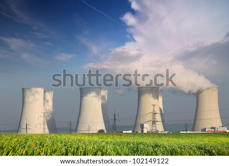 Nuclear power plant with summer field and big blue clouds. - stock photo
