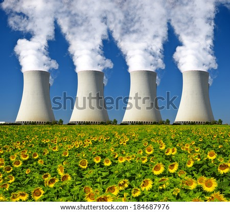 Nuclear power plant with sunflower field - stock photo