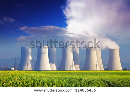 Nuclear power plant with yellow field and big blue clouds - stock photo
