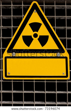 Nuclear radiation sign bolted to steel grid with blank copyspace for your message. - stock photo
