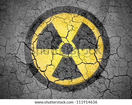 Nuclear radiation symbol painted on cracked ground with vignette - stock photo