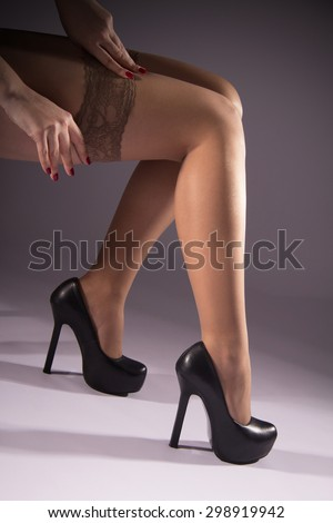 Nude female legs, slender legs, puts a nylon stocking, vertical image, smooth skin, grey background, healthy skin, red manicure, high heels, European style, pair of legs, attractive shape.