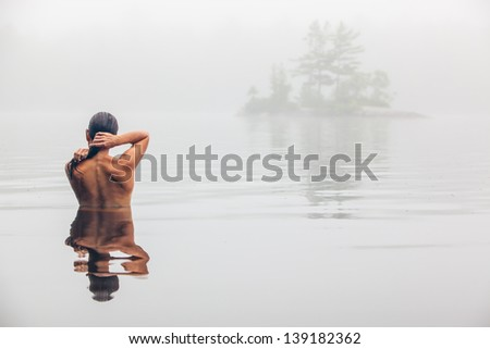 Nude middle aged Caucasian woman bathing and washing hair in Maine lake on a foggy Summer morning. - stock photo