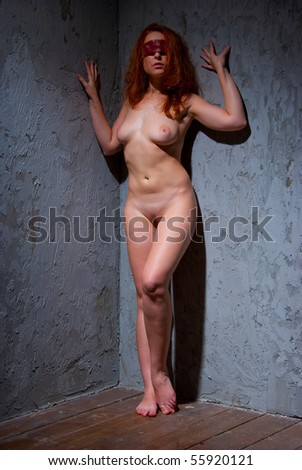 Nude redhead blindfolded girl in a basement - stock photo