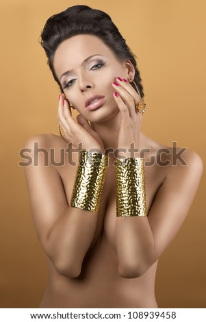 nude sexy girl with two big golden bracelets and hoope earrings, she is in front of the camera, looks in to the lens and her hands are near the face