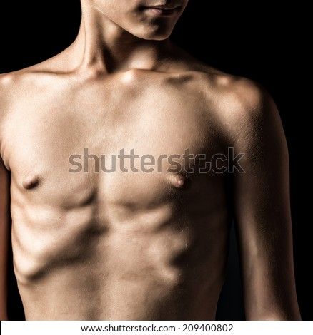 Nude torso of a young man isolated on black