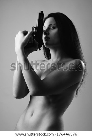 Nude woman is holding a gun both hands in front of her face. She is looking at the camera. - stock photo