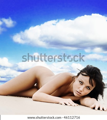 Nude woman laying on beach with blue sky background