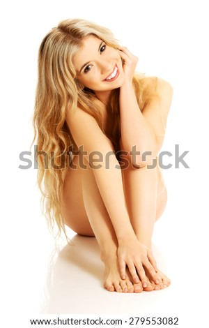 Nude woman sitting with knees close to the chest. - stock photo