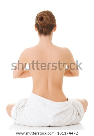 Nude woman with towel practicing yoga
