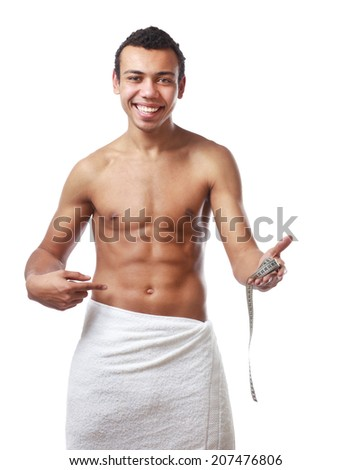 Nude young man covering himself with a towel and tape measuring - stock photo