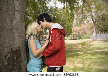 Nuisance cat between couple kissing next to tree in garden or park - stock photo