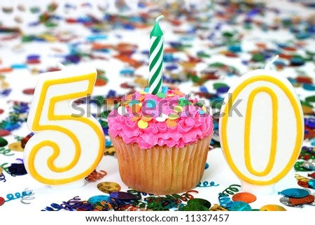 Number 50 celebration cupcake with candle and sprinkles.  Confetti in background.