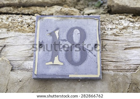 Number eighteen in a wall of a house, detail of a number of information, even number - stock photo