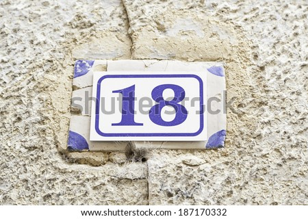 Number eighteen on a wall, detail of a number of information on a wall, even number - stock photo