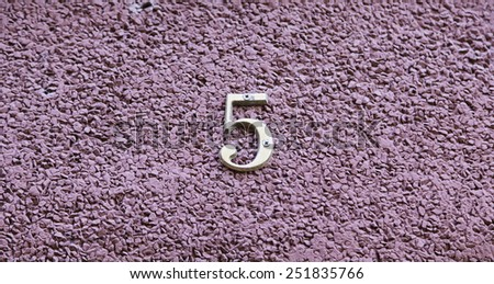 Number five on the wall of a house, detail of a number of information, odd number - stock photo