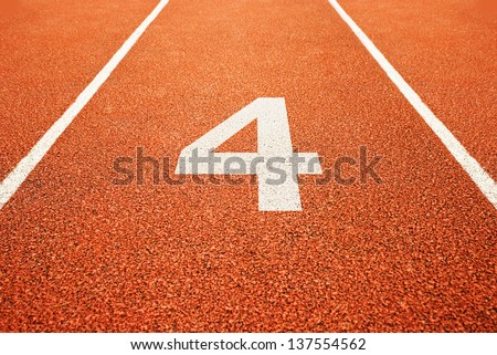 Number four on athletics all weather running track - stock photo