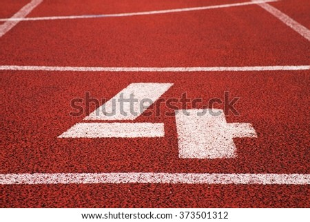 Number four. White track number on red rubber racetrack, texture of racetracks in small stadium
