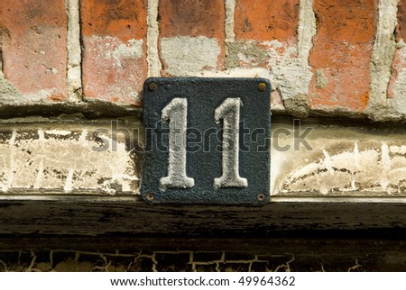 Number 11 house number sign badly damaged by a house fire - stock photo