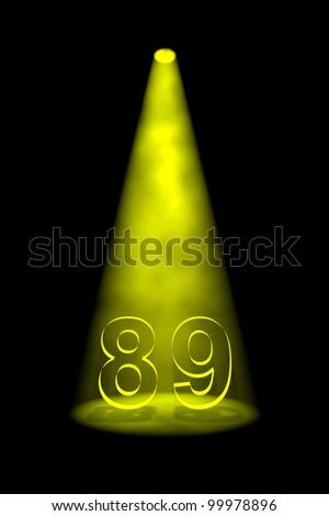 Number 89 illuminated with yellow spotlight on black background - stock photo