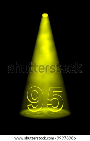 Number 95 illuminated with yellow spotlight on black background - stock photo