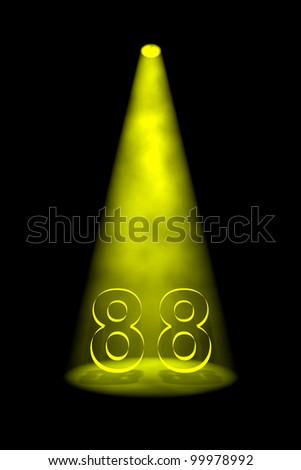 Number 88 illuminated with yellow spotlight on black background - stock photo