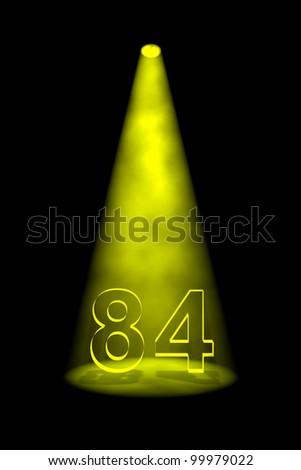 Number 84 illuminated with yellow spotlight on black background - stock photo