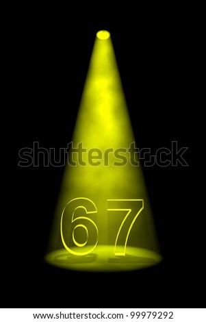 Number 67 illuminated with yellow spotlight on black background - stock photo