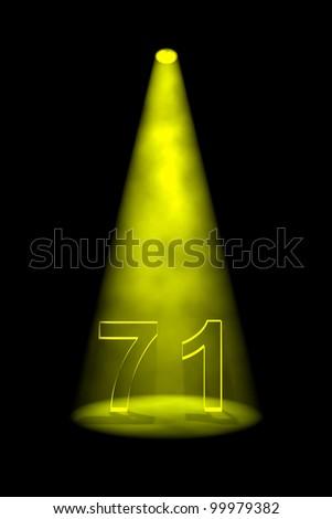 Number 71 illuminated with yellow spotlight on black background - stock photo