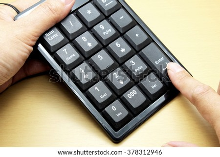 Number keyboard of computer on wooden floor/table, female hand and pressing finger on Enter button. Space for texts. - stock photo
