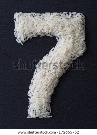 Number 7 made of rice on a black slate - stock photo