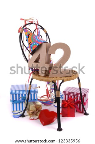 Number of age in a colorful studio setting with paper party hat and figures, a red heart and gifts - stock photo