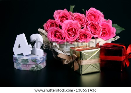 Number of age in a colorful studio setting with pink roses against a black background - stock photo