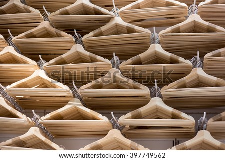 number of empty hangers in the store. Wooden bright  hangers for coat and dress  - stock photo
