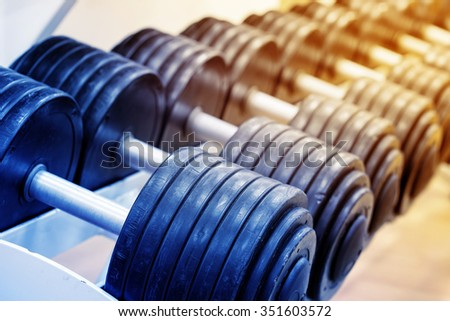Number of heavy dumbbells on rack with ablurred background