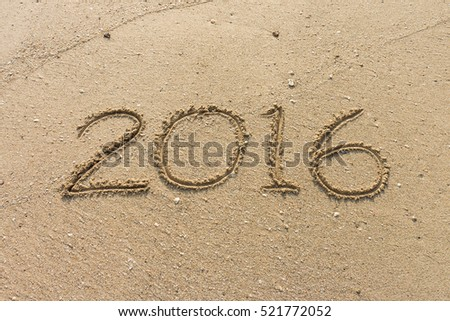 Number of year 2016 written on the sand at the beach