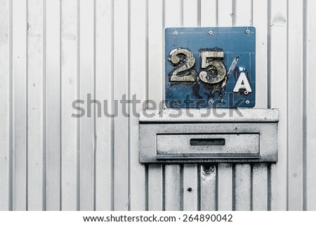 Number 25 old worn house number on blue plaque sign on metal fence surface - stock photo