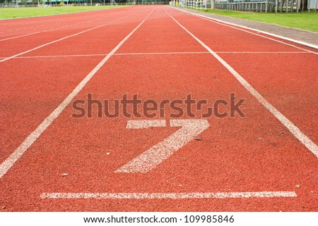 number 7  on red running track - stock photo