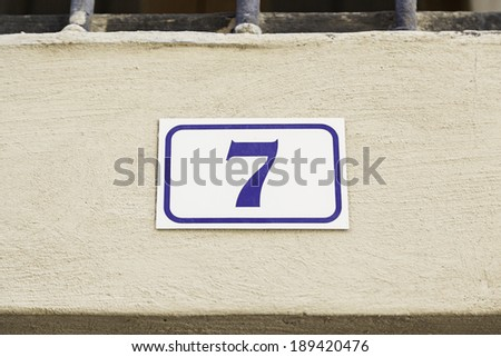 Number seven on a wall, detail of a wall with an information number, odd number - stock photo