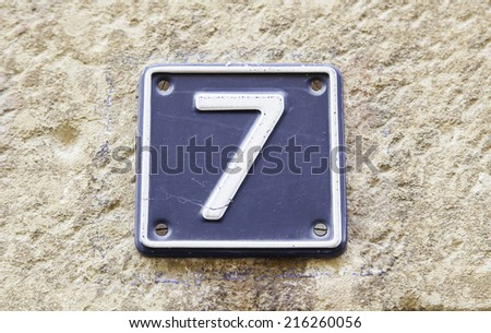 Number seven on a wall of a house, detail of a number of information, odd number - stock photo