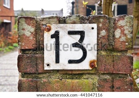 Number 13 sign. House Number Thirteen sign on brick stone wall