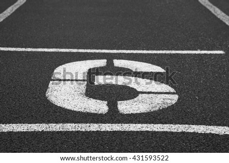 Number six. White athletic track number on red rubber racetrack, texture of racetracks in small stadium. Black and white photo - stock photo