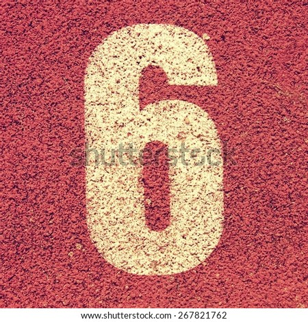 Number six. White track number on red rubber racetrack, texture of running racetracks in small stadium - stock photo