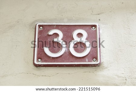 Number thirty-eight on the wall of a house, detail of a number of information, even number - stock photo