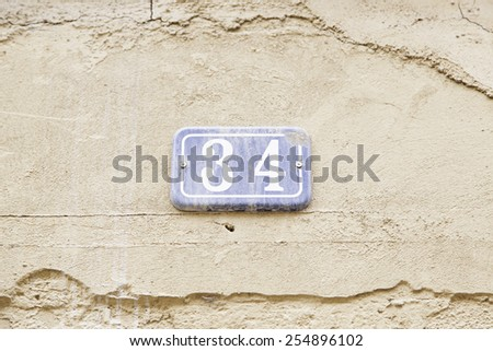 Number thirty-four on the wall of a house, detail of a number of information, even number - stock photo