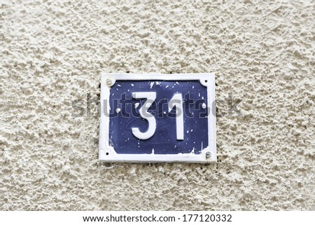Number thirty-one on a wall, detail of a wall of a house with a number of information - stock photo